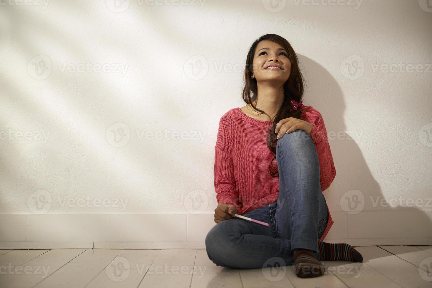 feliz chica asiática con prueba de embarazo en casa foto