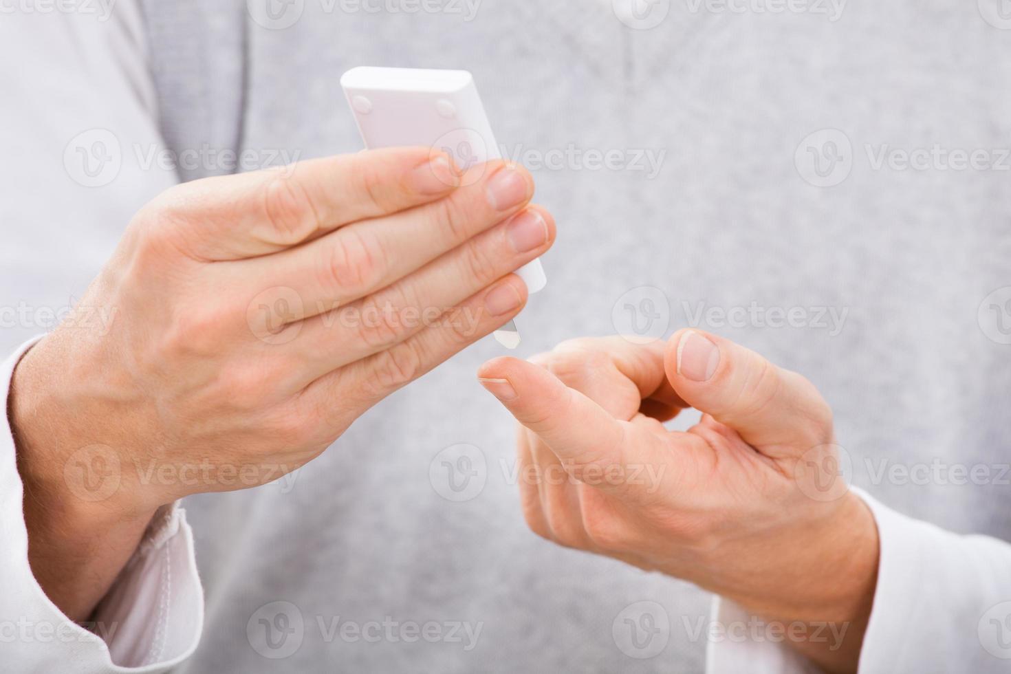 Man Examining Blood Sugar Level photo