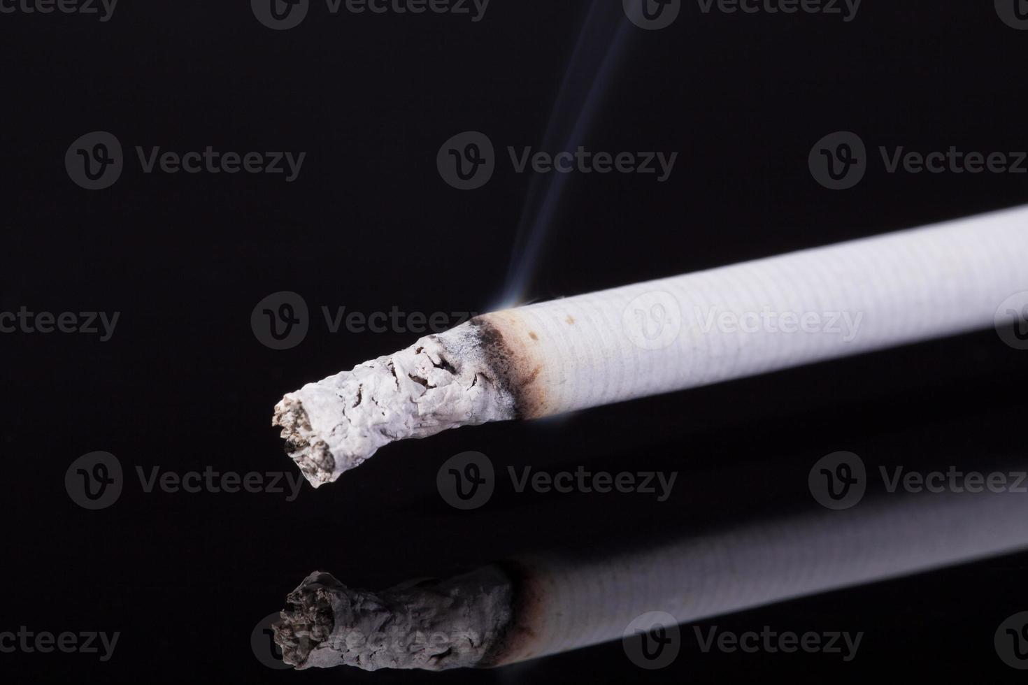 lit single cigarette with smoke  on black background photo