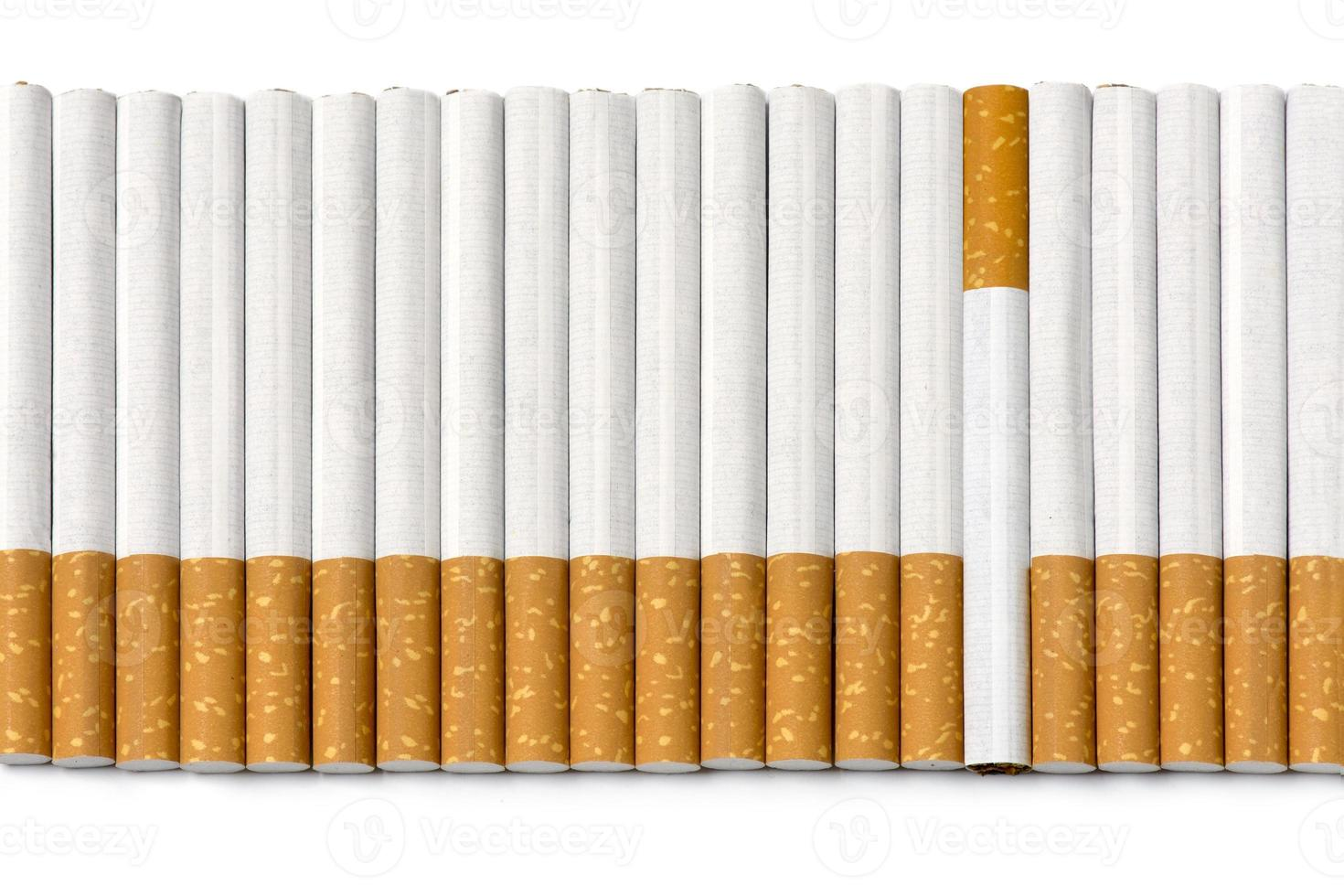 fila de cigarrillos con filtro, uno está al revés, en blanco foto