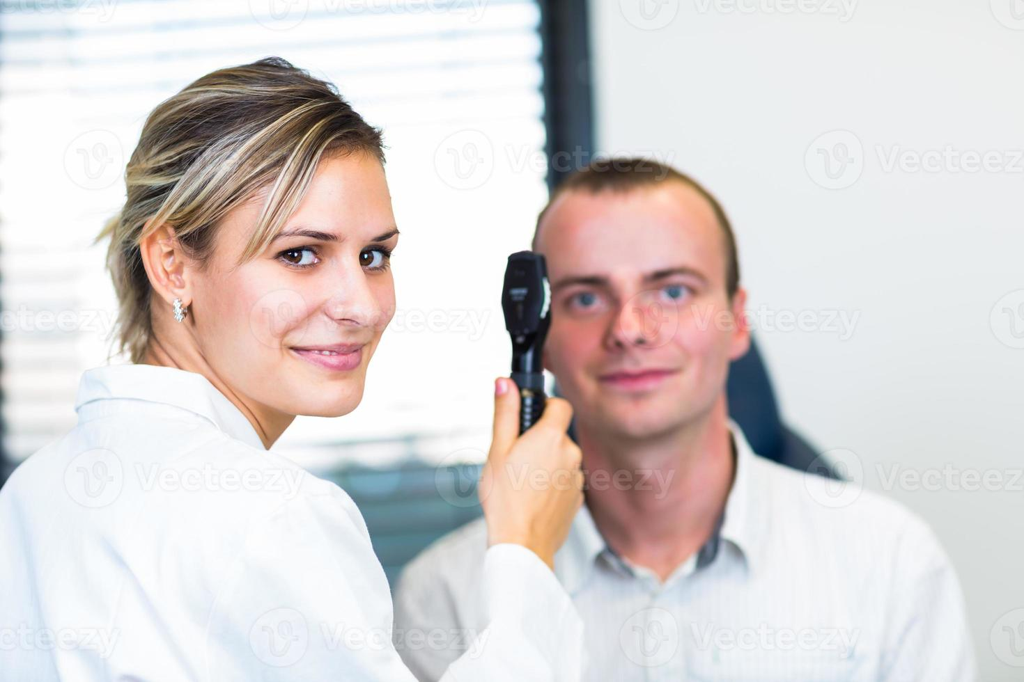 Optometry concept - pretty young woman having her eyes examined photo