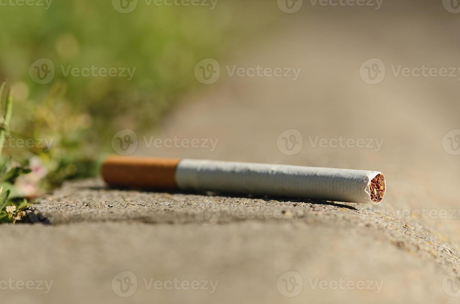 Cigarette on asphalt photo
