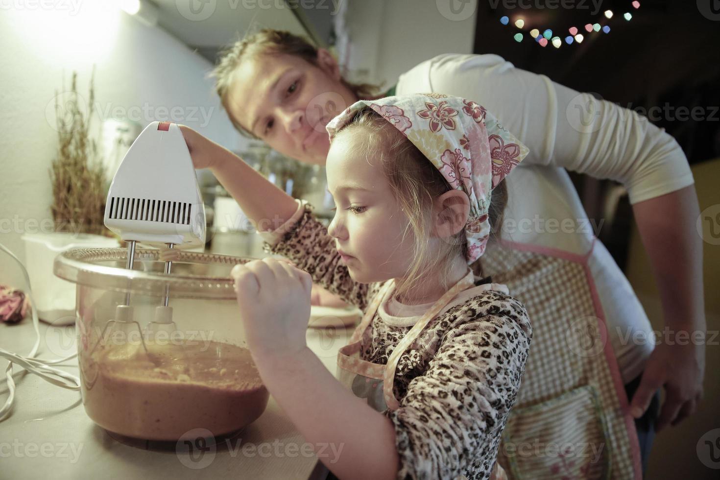 madre enseñando a su hija en la cocina foto