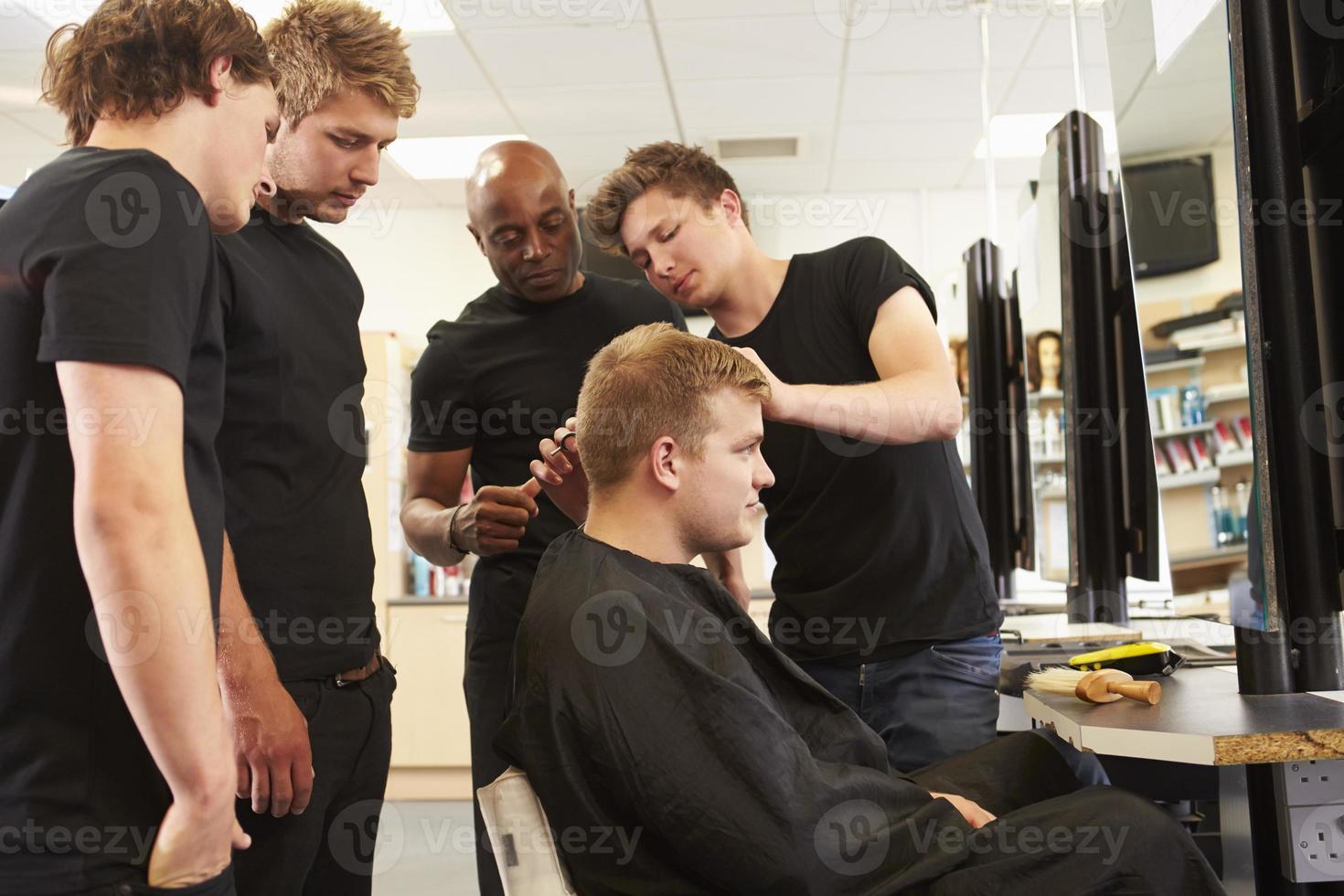 profesor ayudando a estudiantes a entrenarse para convertirse en peluqueros foto