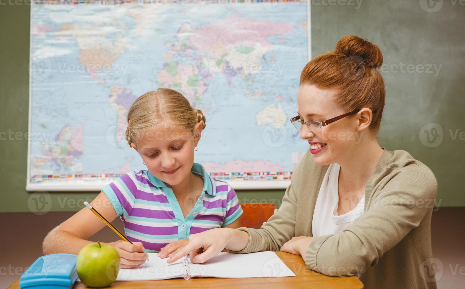Teacher assisting girl with homework in classroom photo