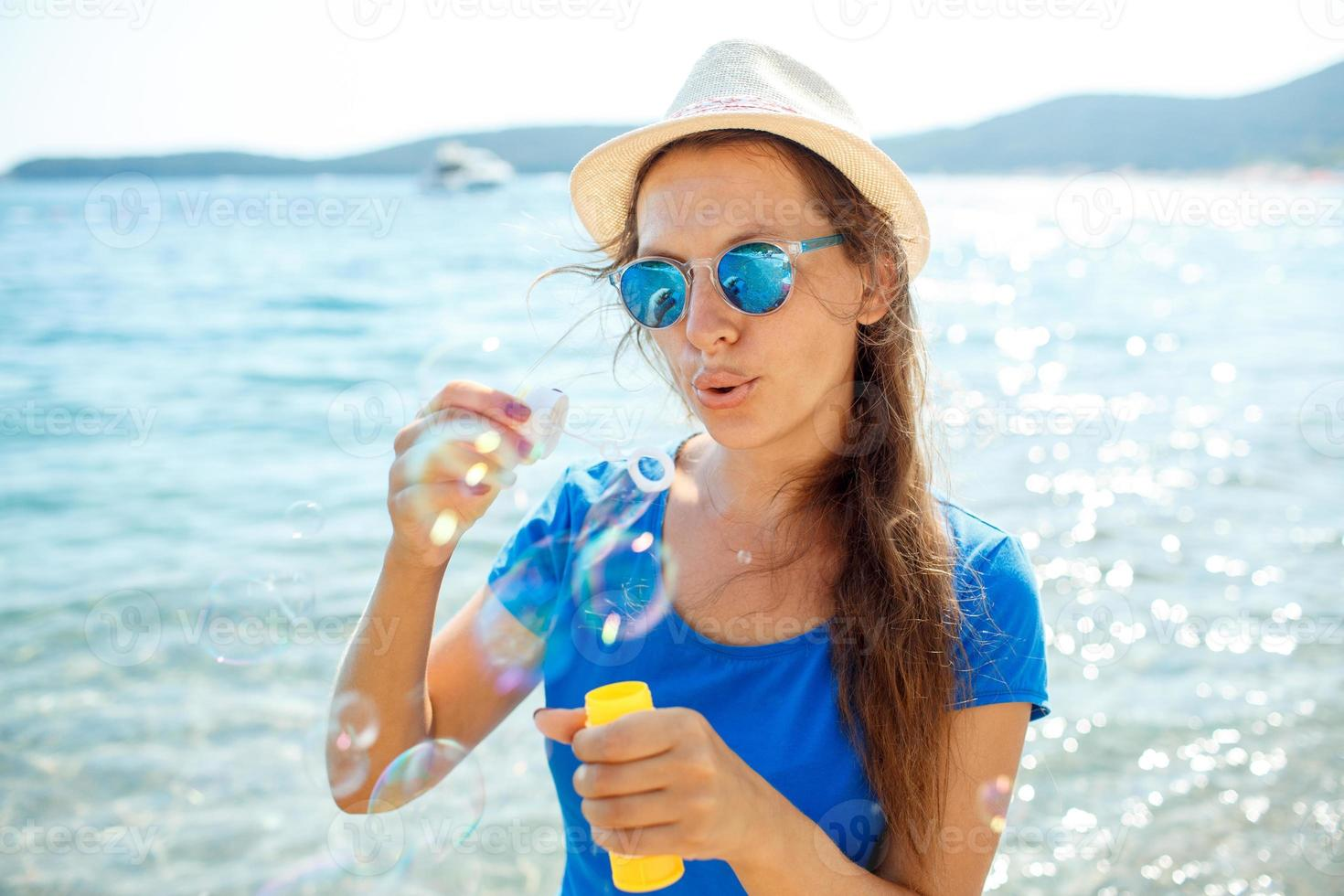 Happy young girl blowing soap bubbles on the seashore photo