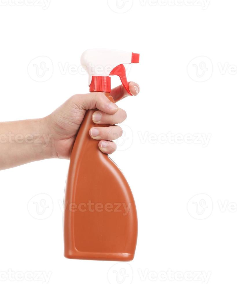 Mano sosteniendo la botella de spray de plástico marrón. foto