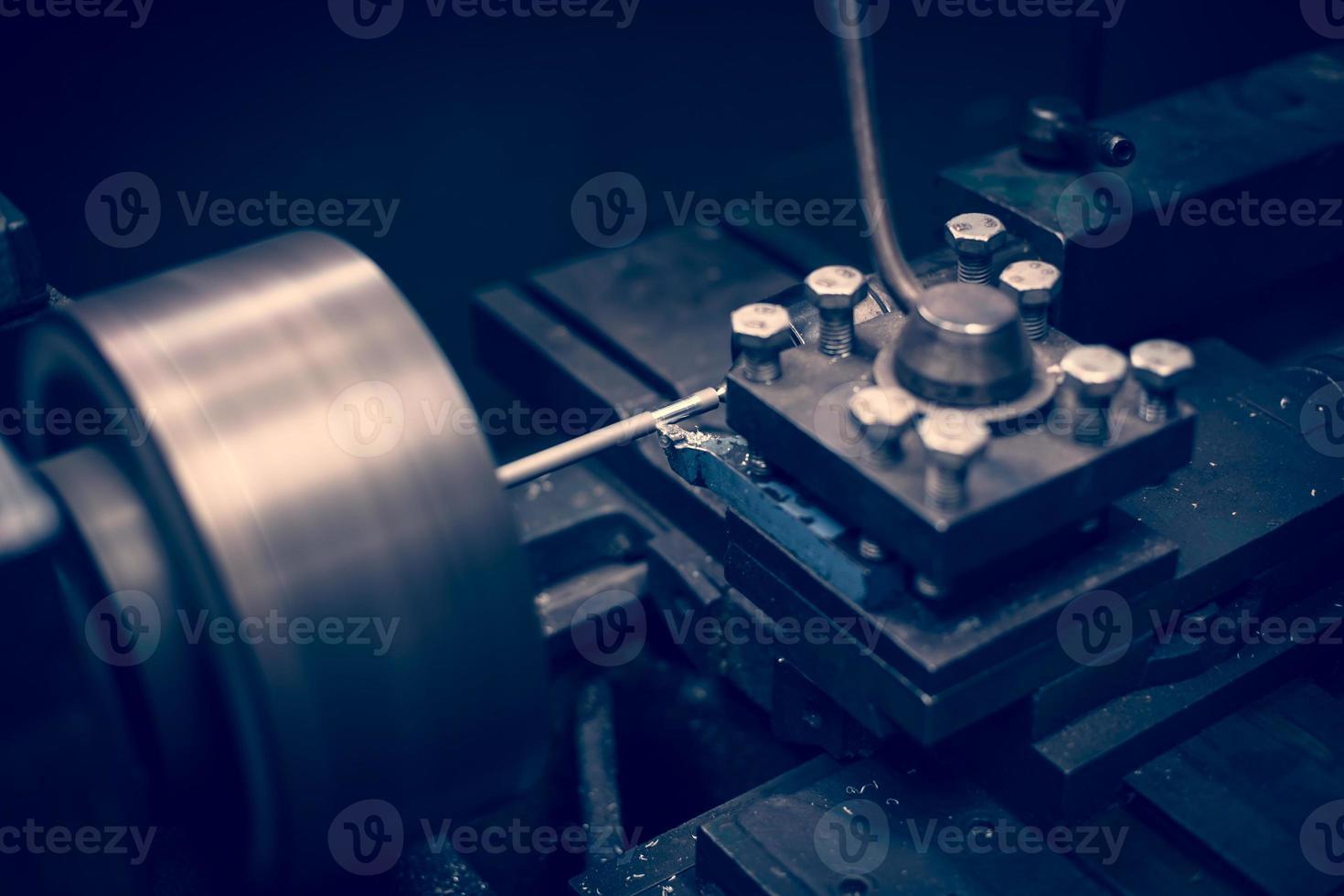 Lathe machine operates on steel rod. photo