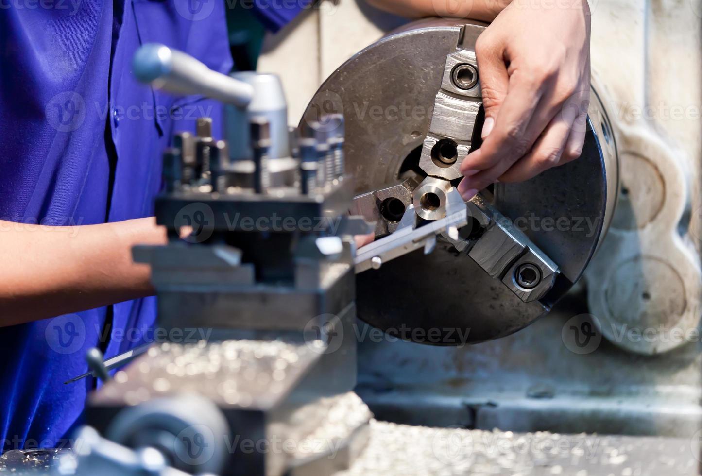 Milling machine operator working in factory workshop photo