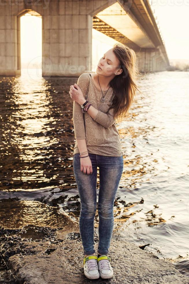 Young sensual woman standing on the stone near water photo
