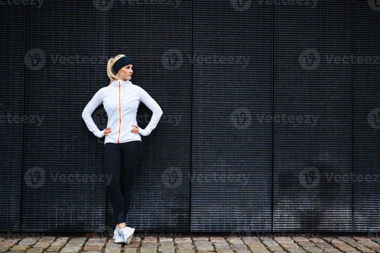 mujer decidida descansando después de trotar en la ciudad foto