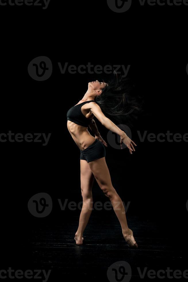 young ballet dancer dansing on black background photo