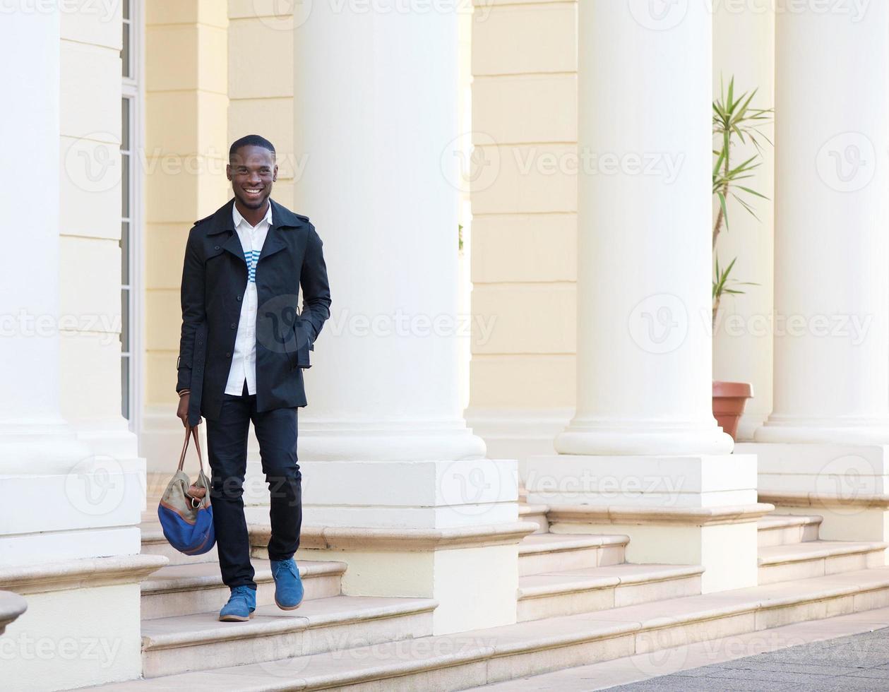 hombre feliz caminando afuera del hotel con bolsa foto
