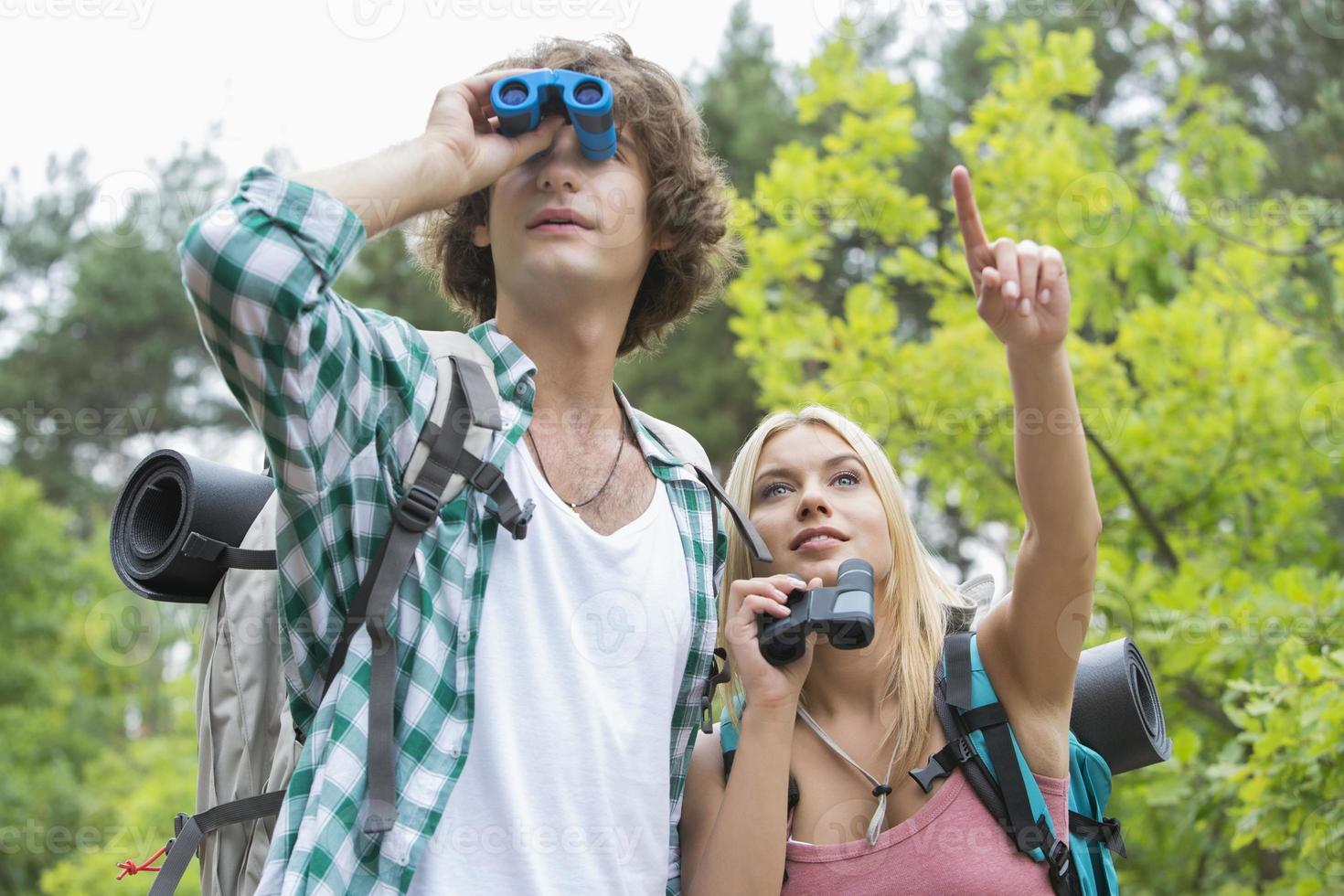 excursionista masculino utilizando binoculares mientras novia mostrando algo en el bosque foto