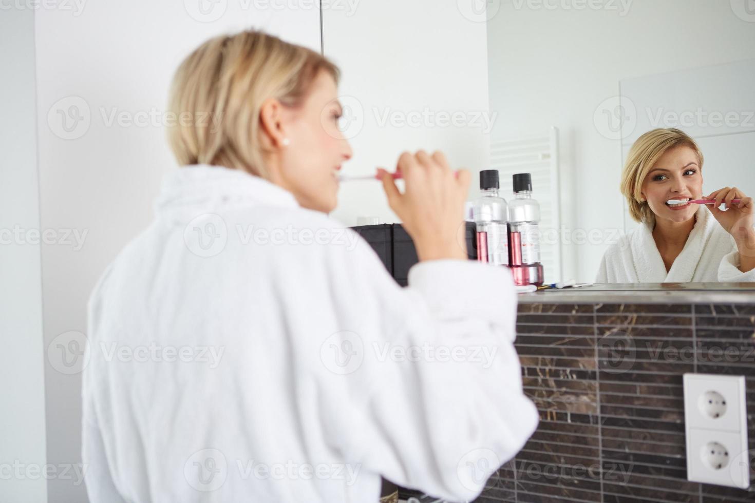 mujer joven cepillarse los dientes foto