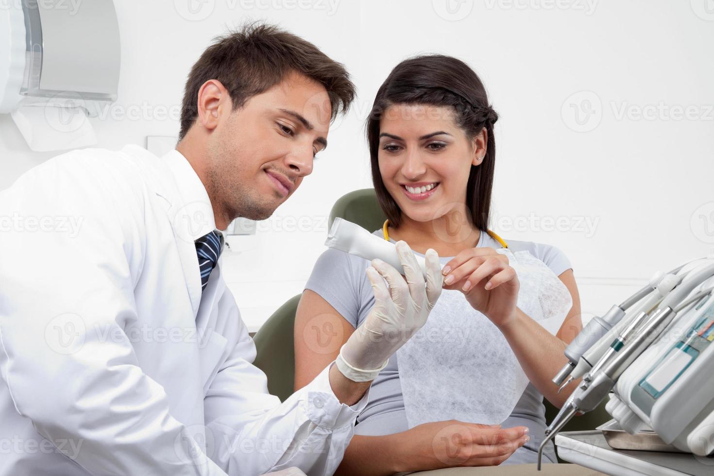 dentista prescribe pasta de dientes al paciente foto