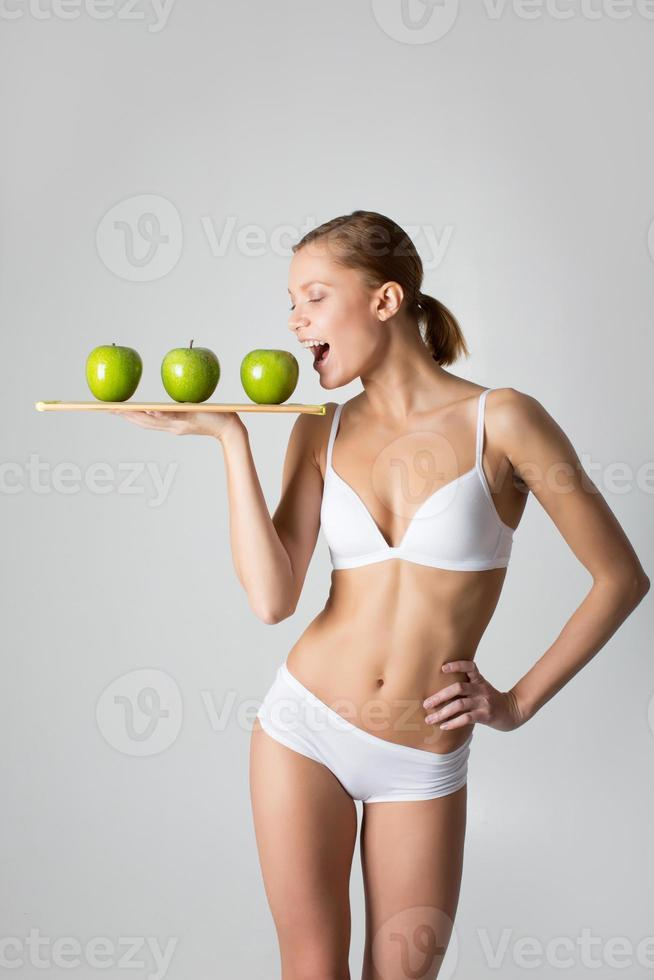 young slim girl holding a green apple photo