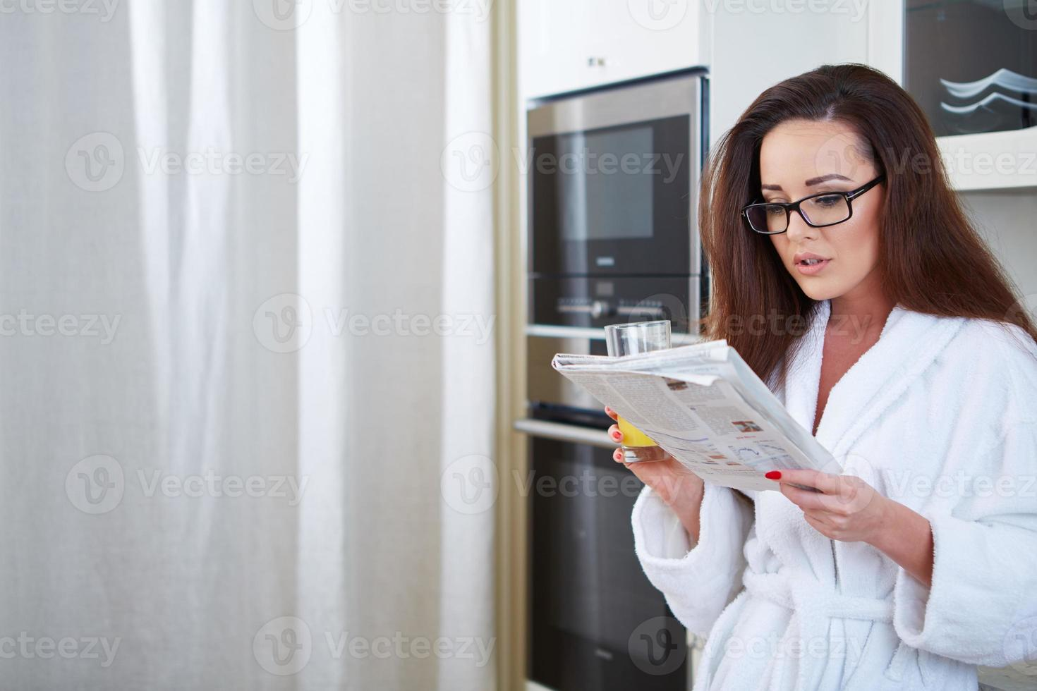 Mujer leyendo las noticias mientras bebe zumo de naranja foto