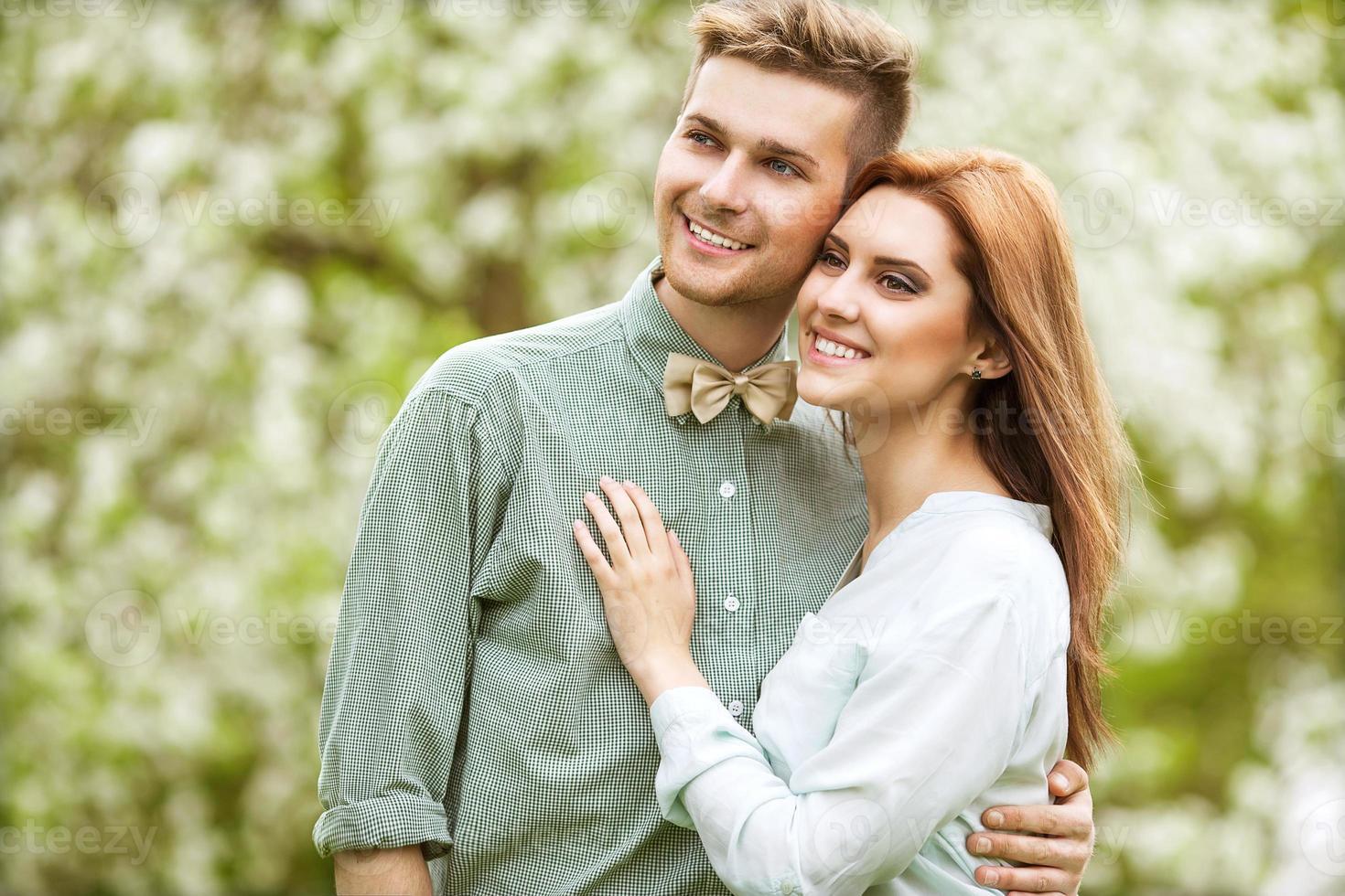 pareja de enamorados en el parque sonriendo sosteniendo un ramo foto