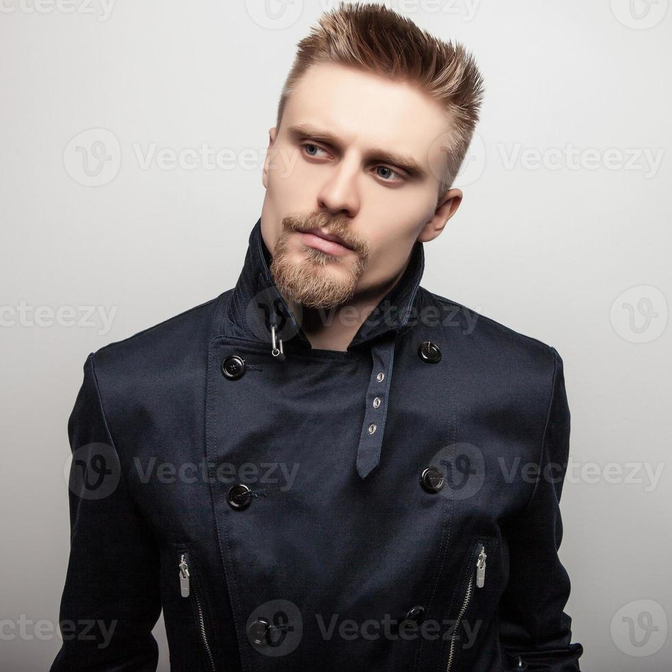 elegante joven guapo con abrigo negro. Retrato de moda de estudio. foto