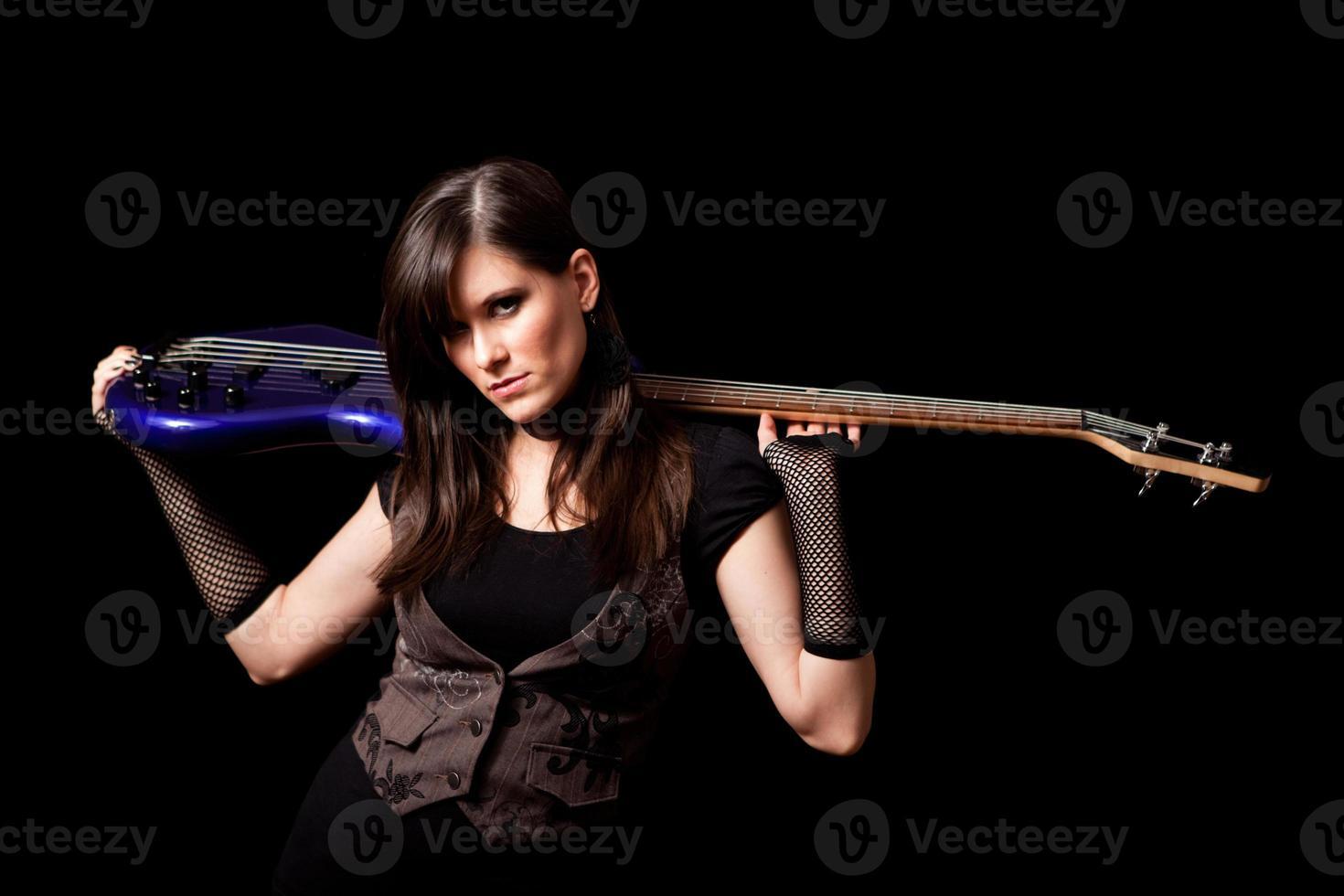 Tough Rocker Girl Holding Bass Guitar Behind Her Neck photo