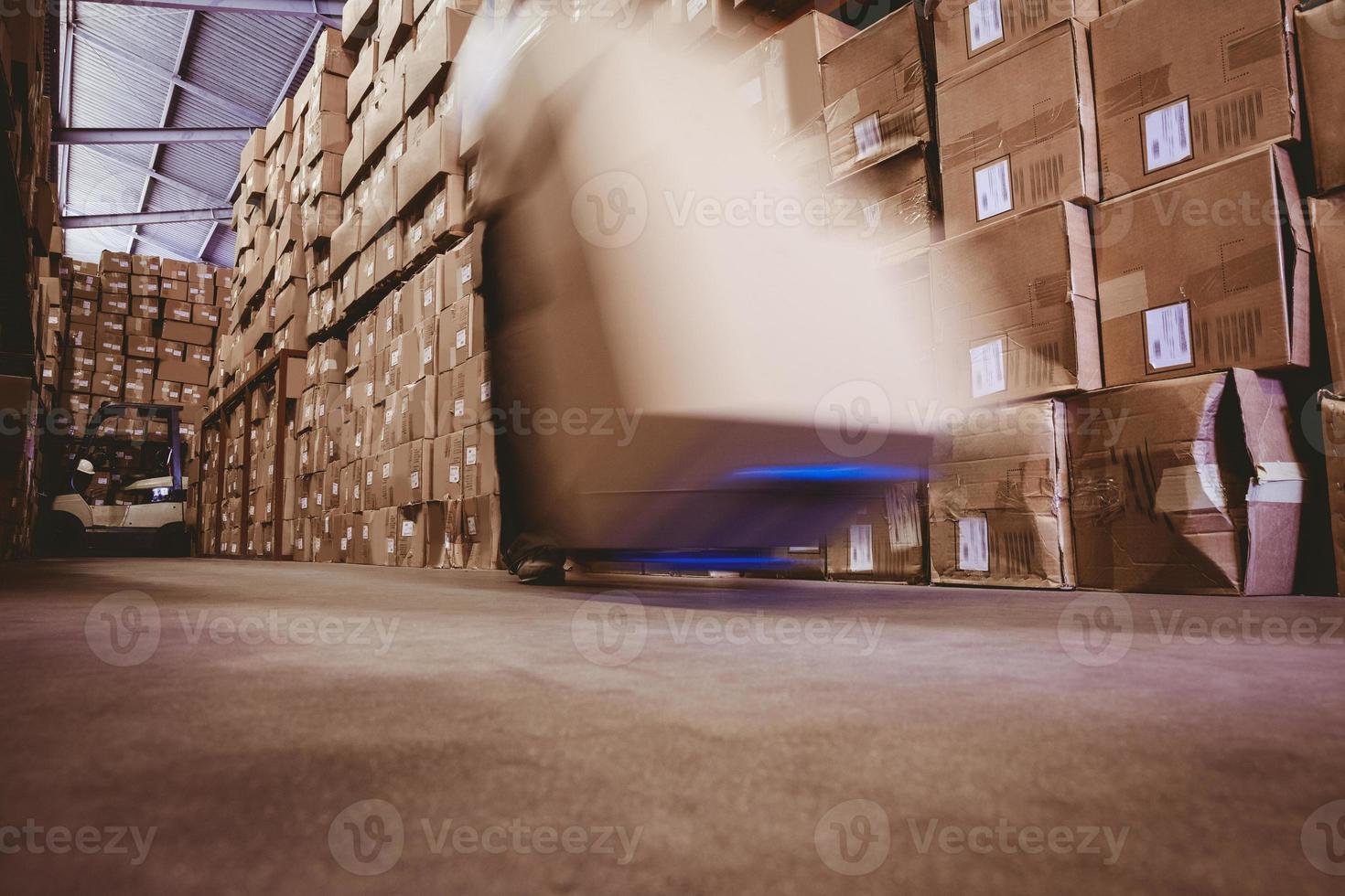 Trabajador con apilador de transpaleta en almacén foto