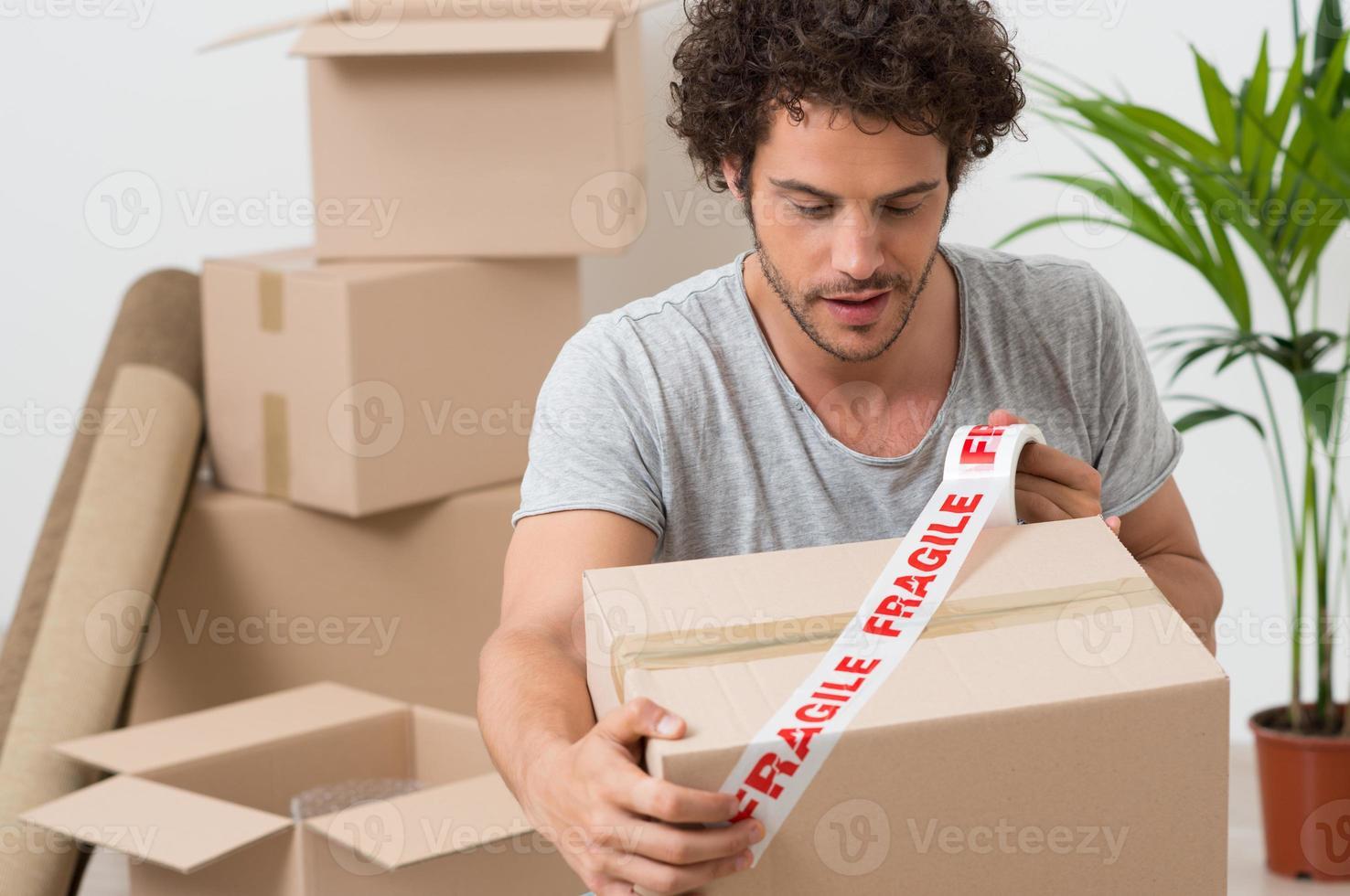 Young Man Packing Cardboard Box photo