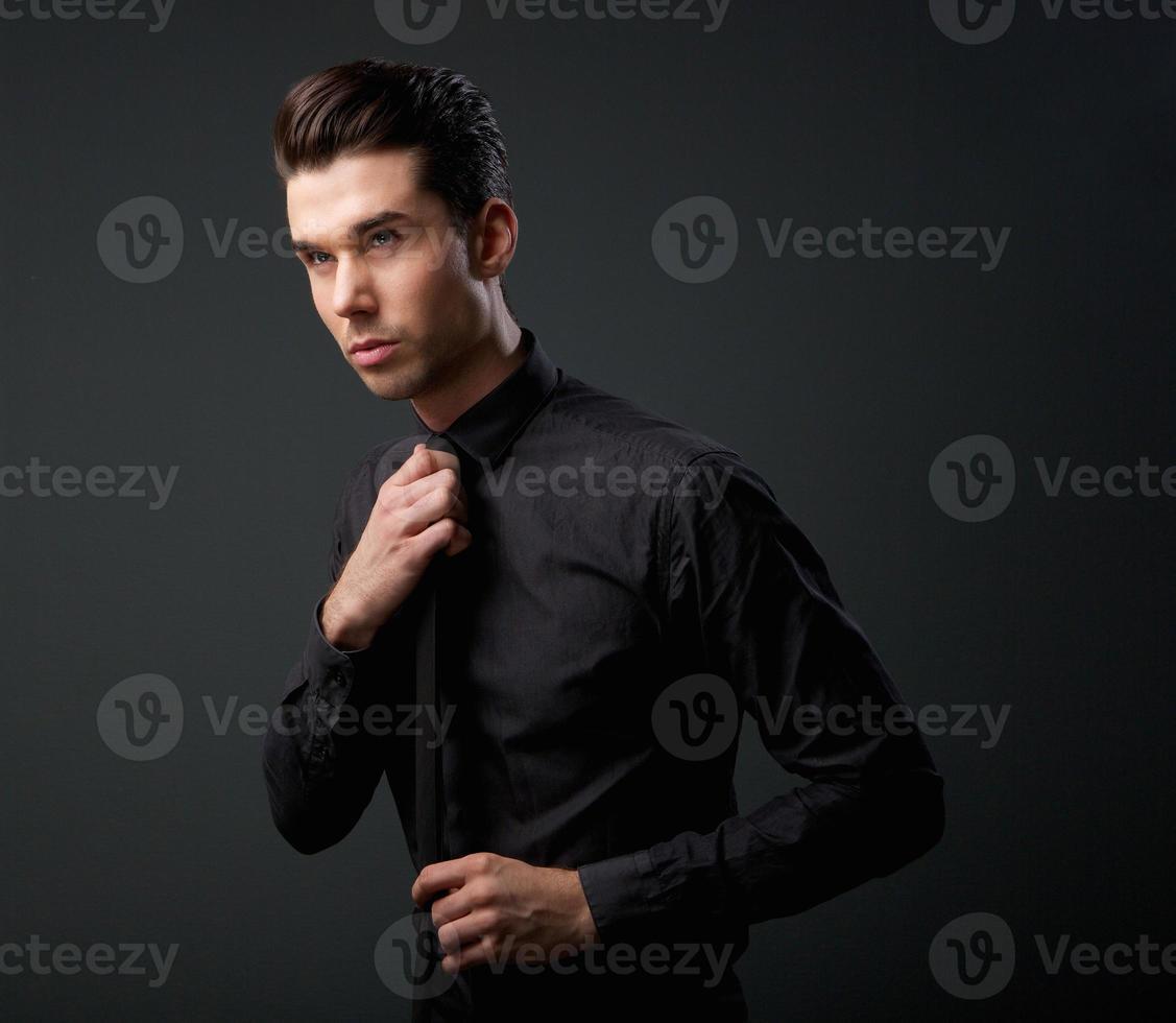 joven genial con camisa negra y corbata foto