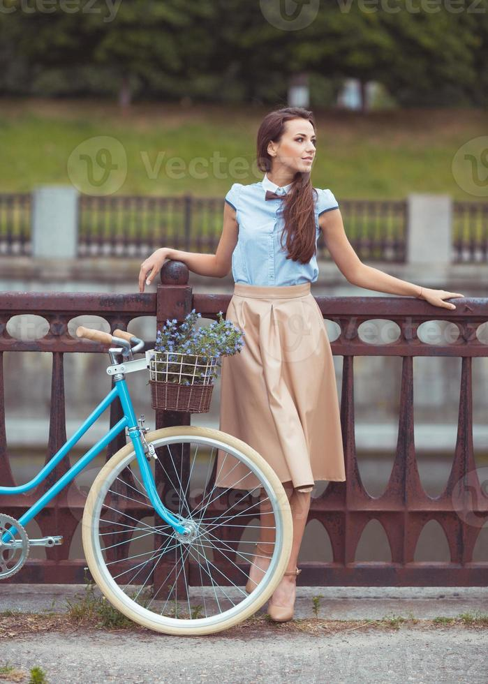 Young beautiful, elegantly dressed woman with bicycle photo