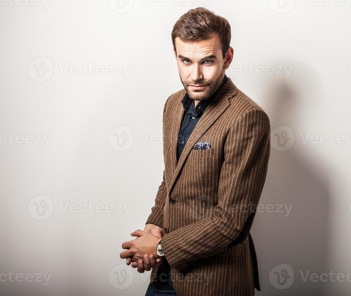 Elegante joven guapo en traje de lujo. Retrato de moda de estudio. foto