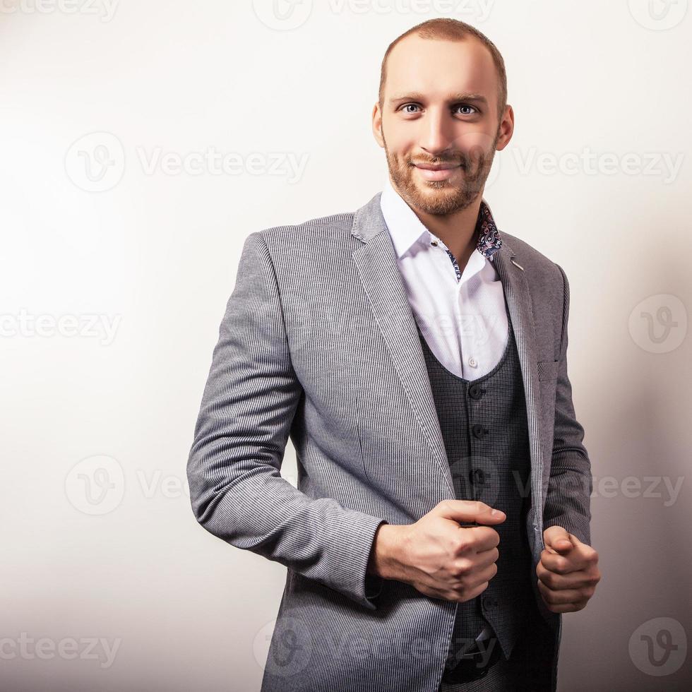 Elegante joven guapo en traje gris. foto