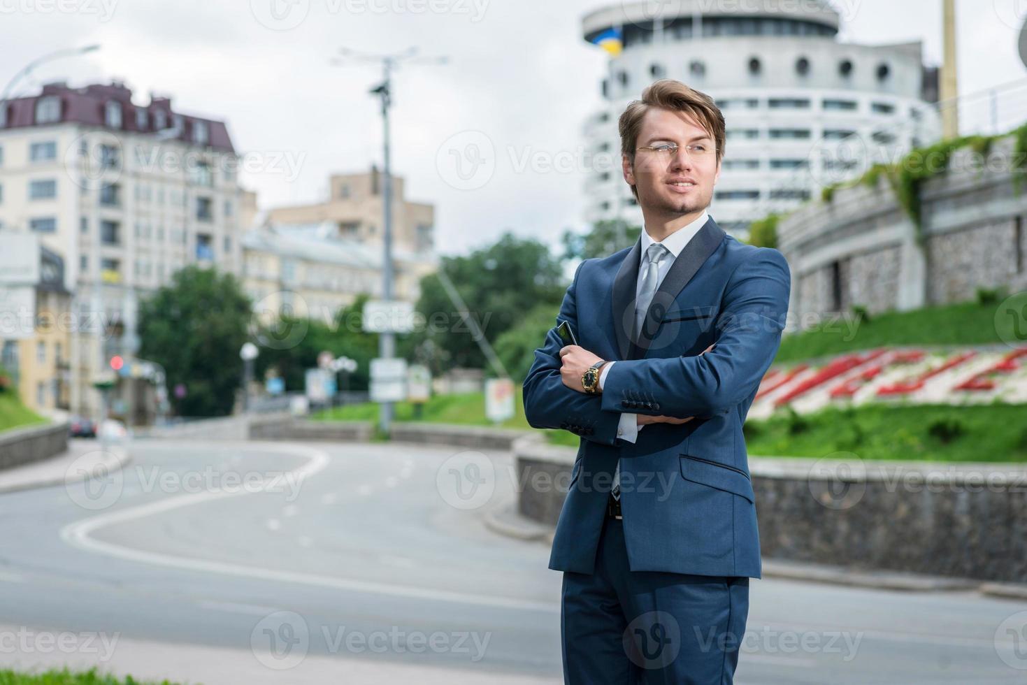 joven en traje formal está de pie junto a la carretera foto