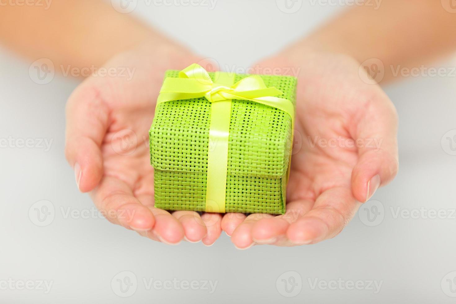 colorido regalo verde en manos ahuecadas foto