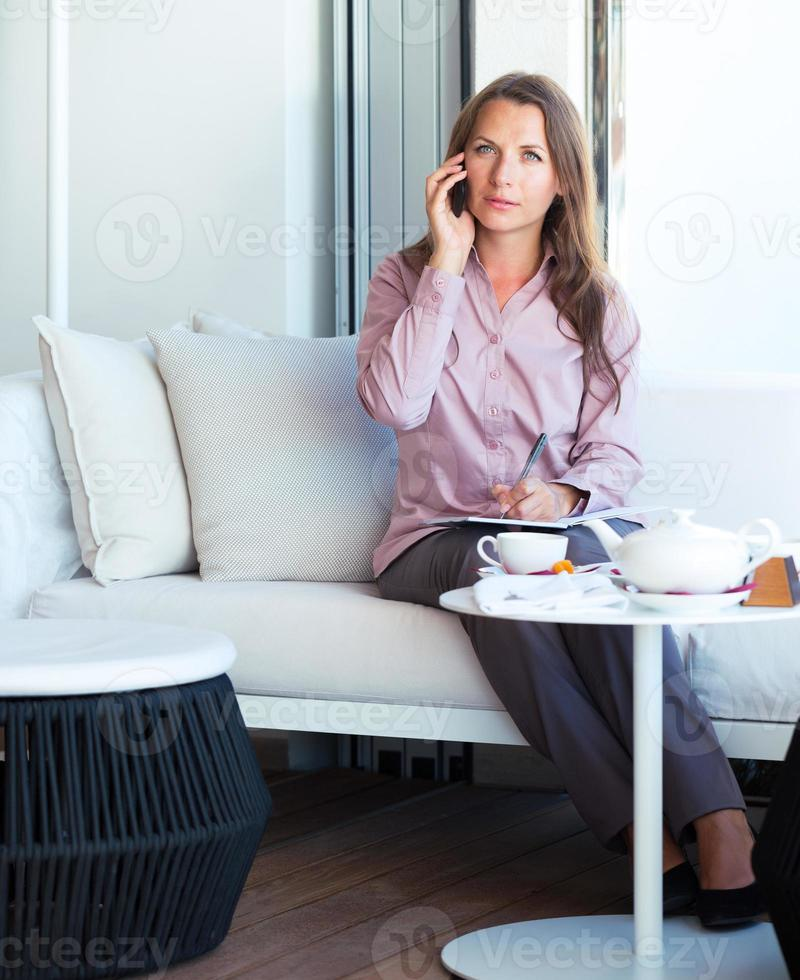 Businesswoman talking on the cellphone in a coffee house photo