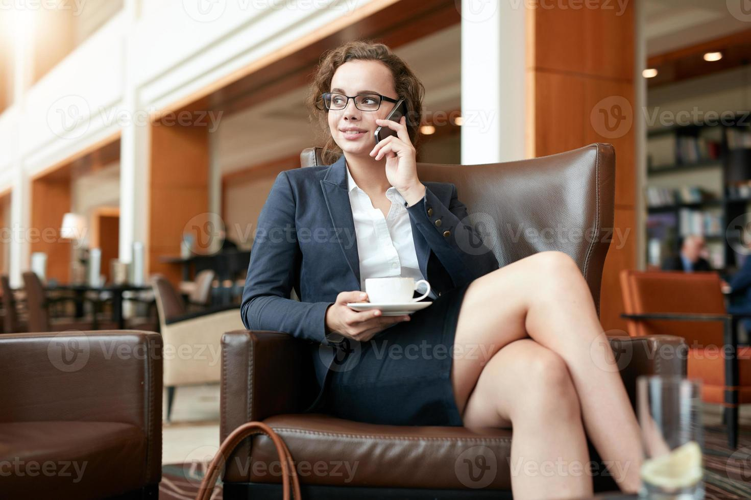 Businesswoman sitting in cafe talking on mobile phone photo