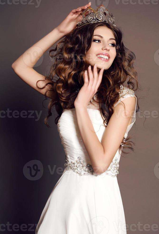 mujer con cabello oscuro en elegante vestido con lujosa corona foto