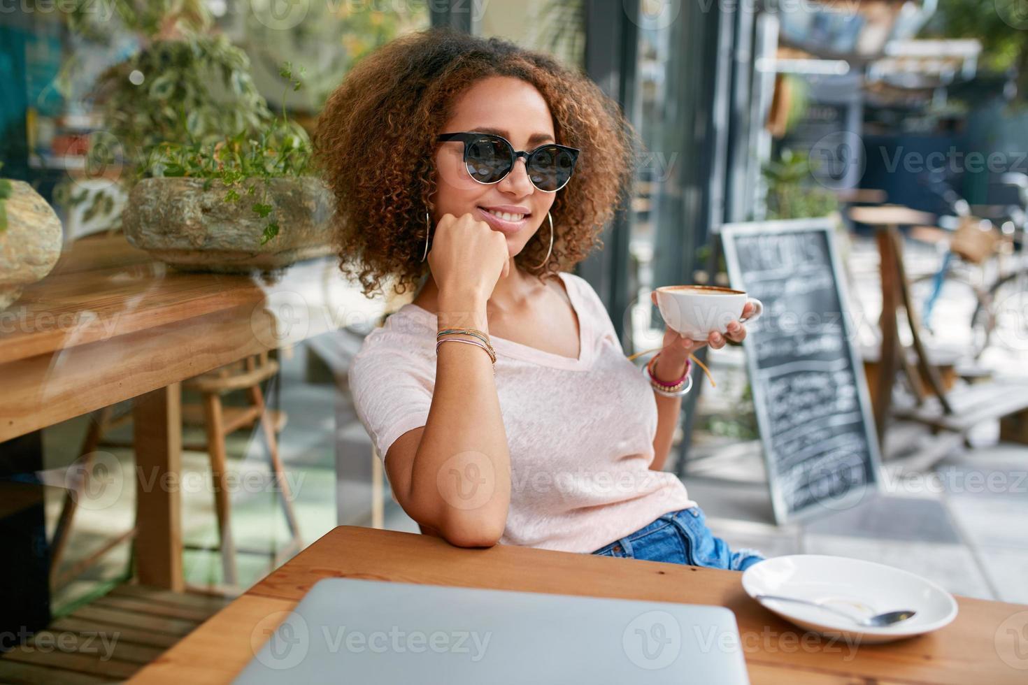 hermosa chica tomando una taza de café en la cafetería foto