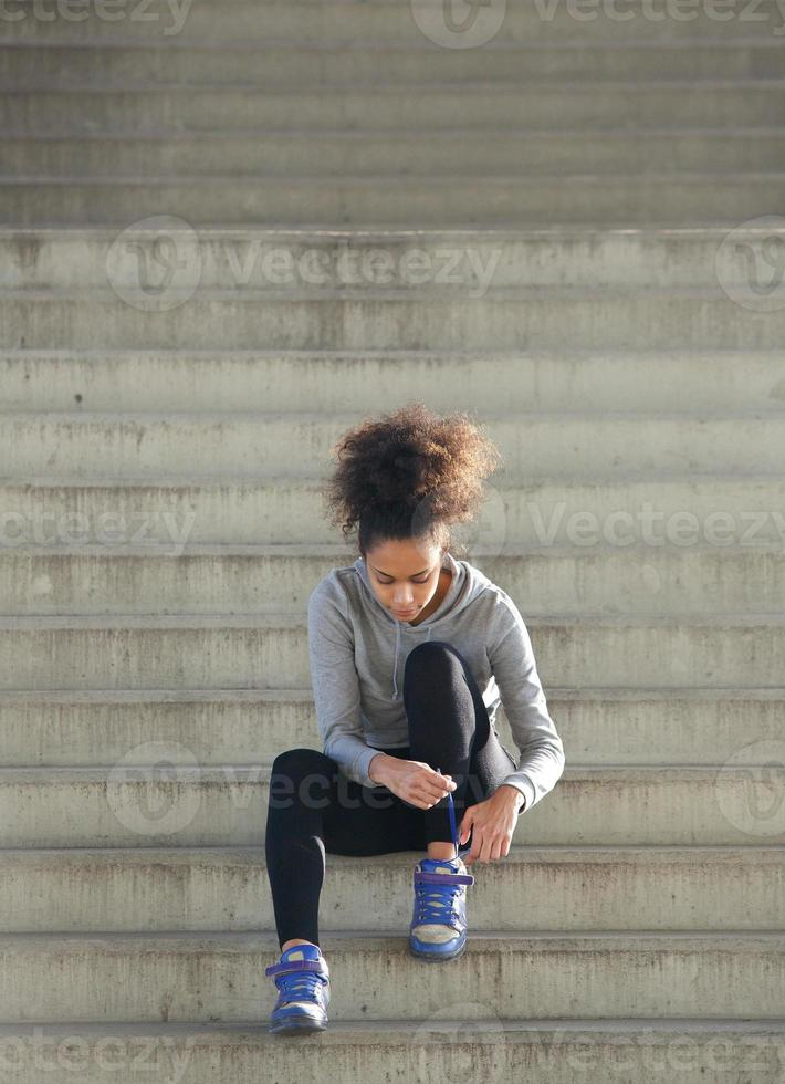 Young sports woman tying shoelaces on steps photo