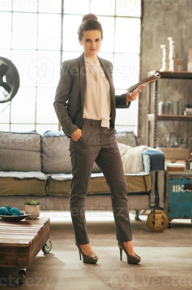 Retrato de cuerpo entero de mujer de negocios de pie con la revista foto