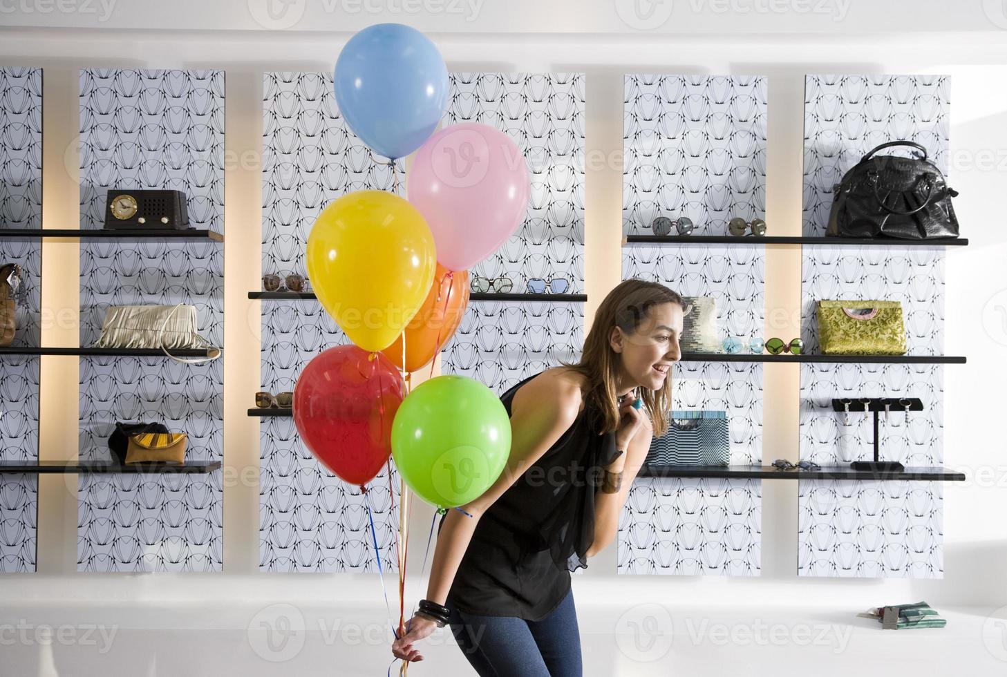mujer joven feliz en boutique con globos foto