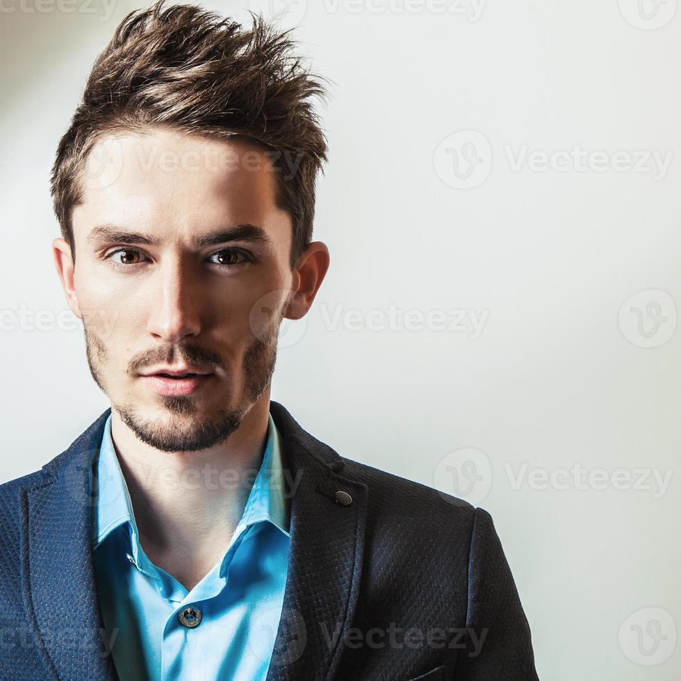 Elegante joven guapo en traje. Retrato de moda de estudio. foto