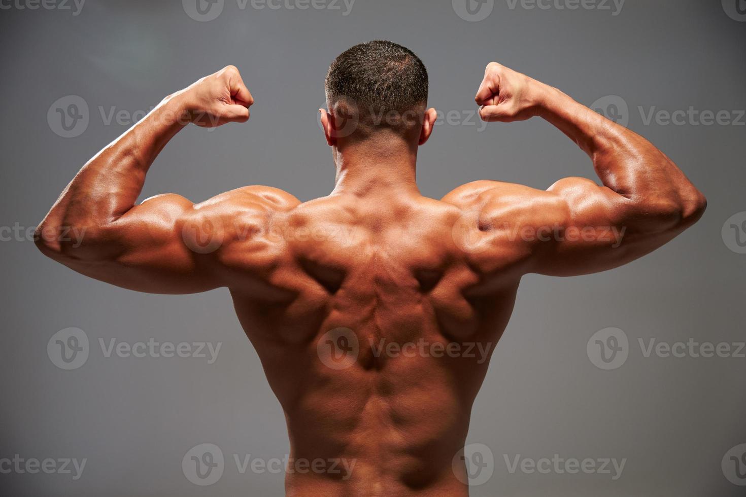 culturista masculino flexionando sus bíceps, vista posterior foto