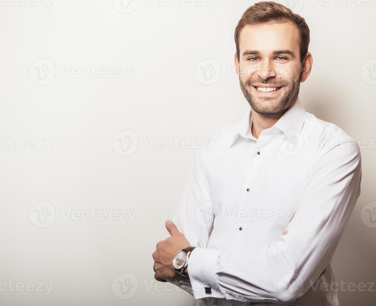 Elegante joven guapo en camisa blanca. Retrato de moda de estudio. foto