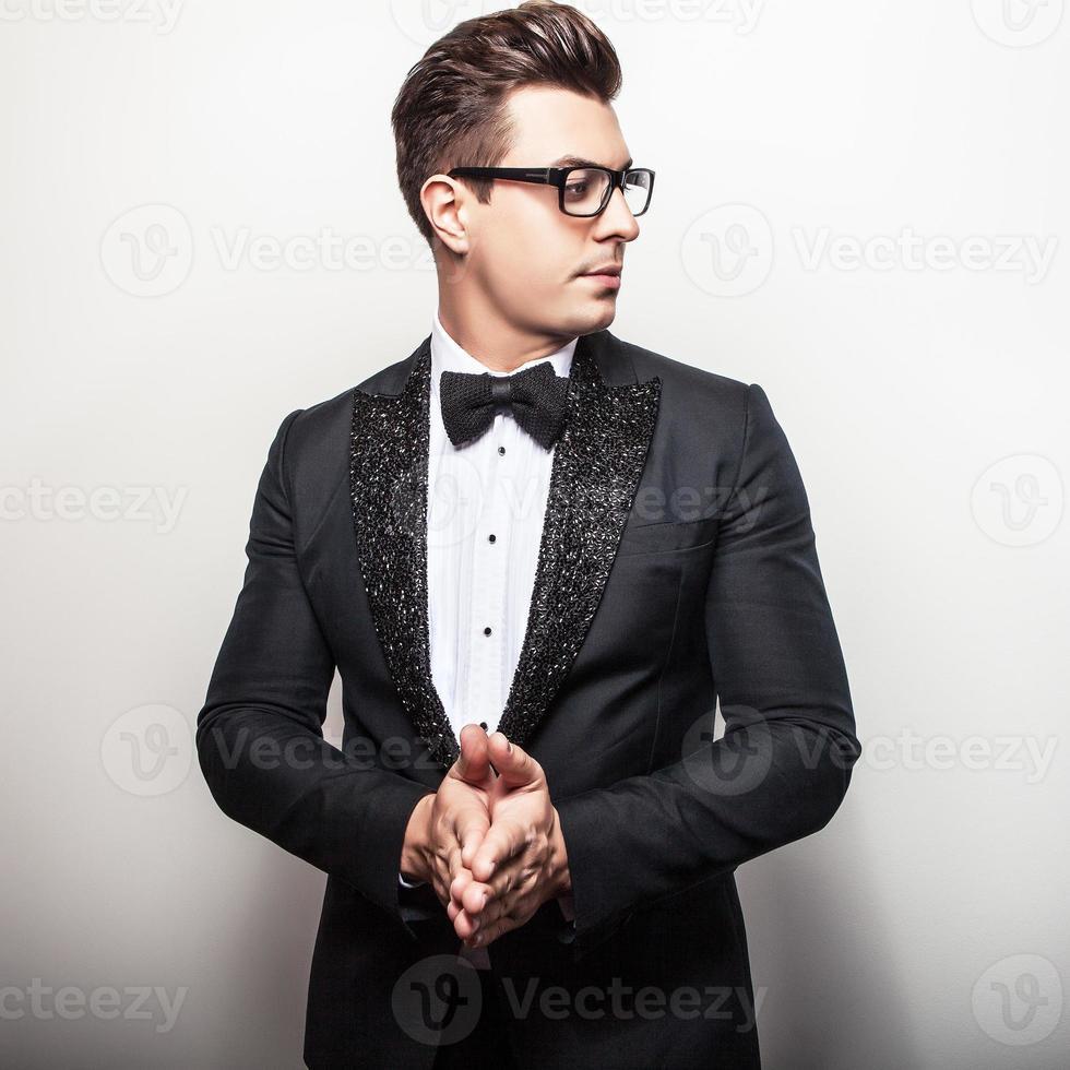 Elegant young handsome man in black luxury costume. photo