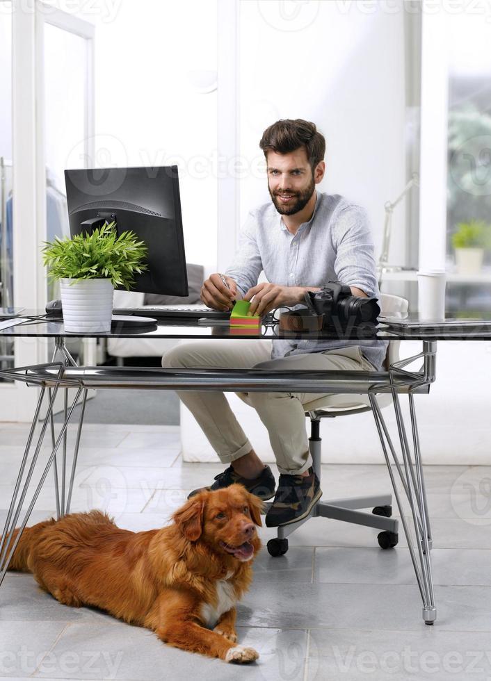 empresario trabajando en el lugar de trabajo que admite mascotas foto