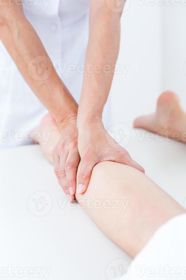 fisioterapeuta haciendo masaje de piernas foto
