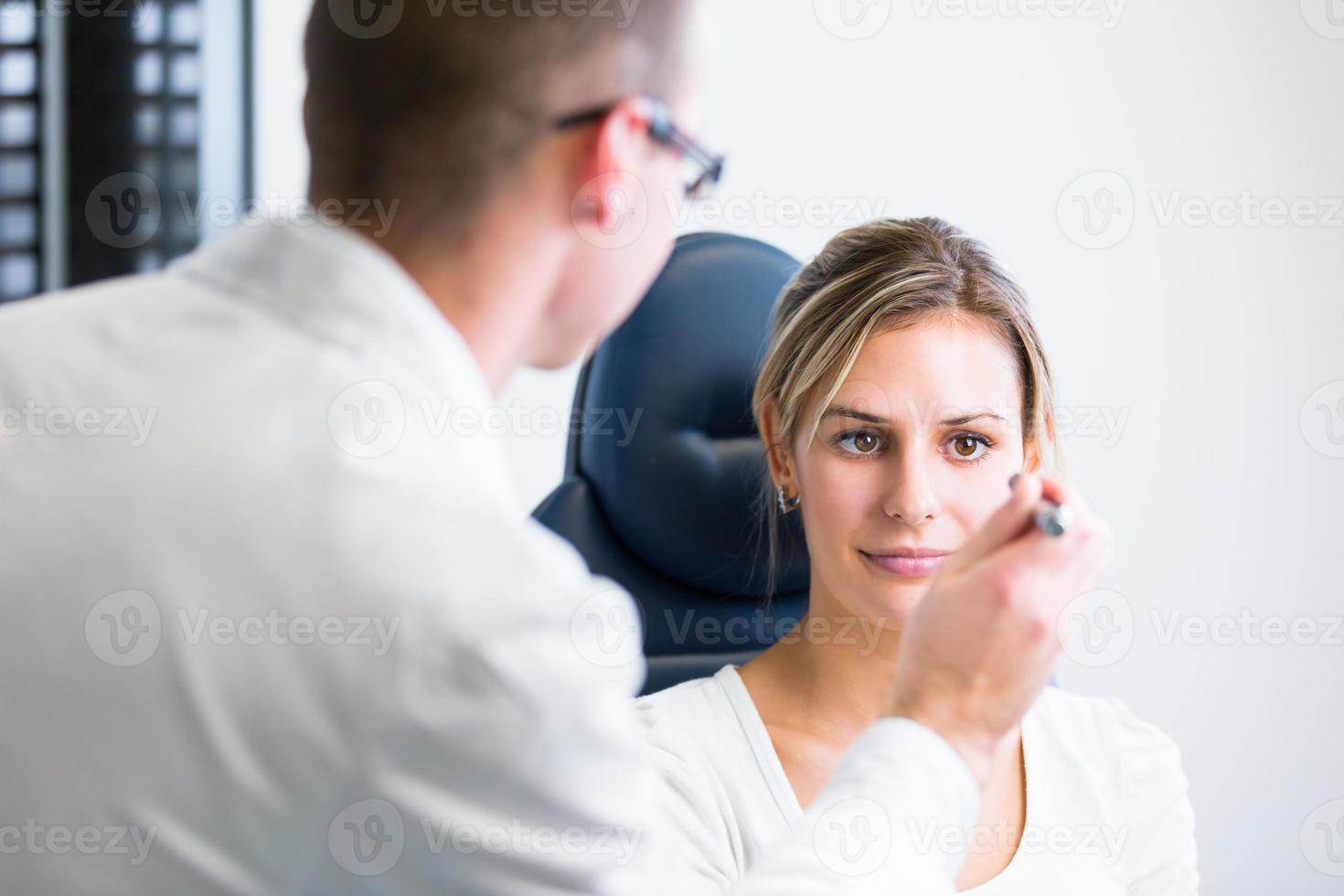 concepto de optometría - mujer bastante joven que tiene sus ojos examinados foto