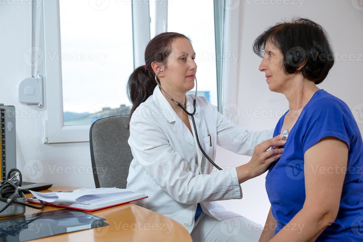 Joven médico examina a su paciente mayor con un estetoscopio foto