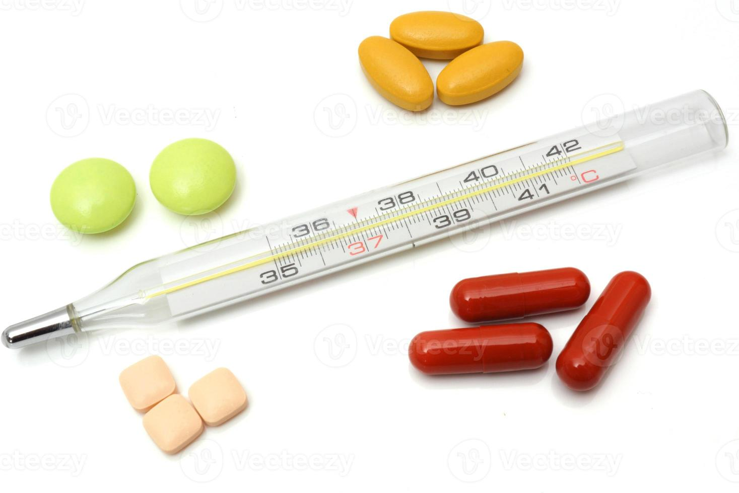 concepto de enfermedad con termómetro y tabletas foto
