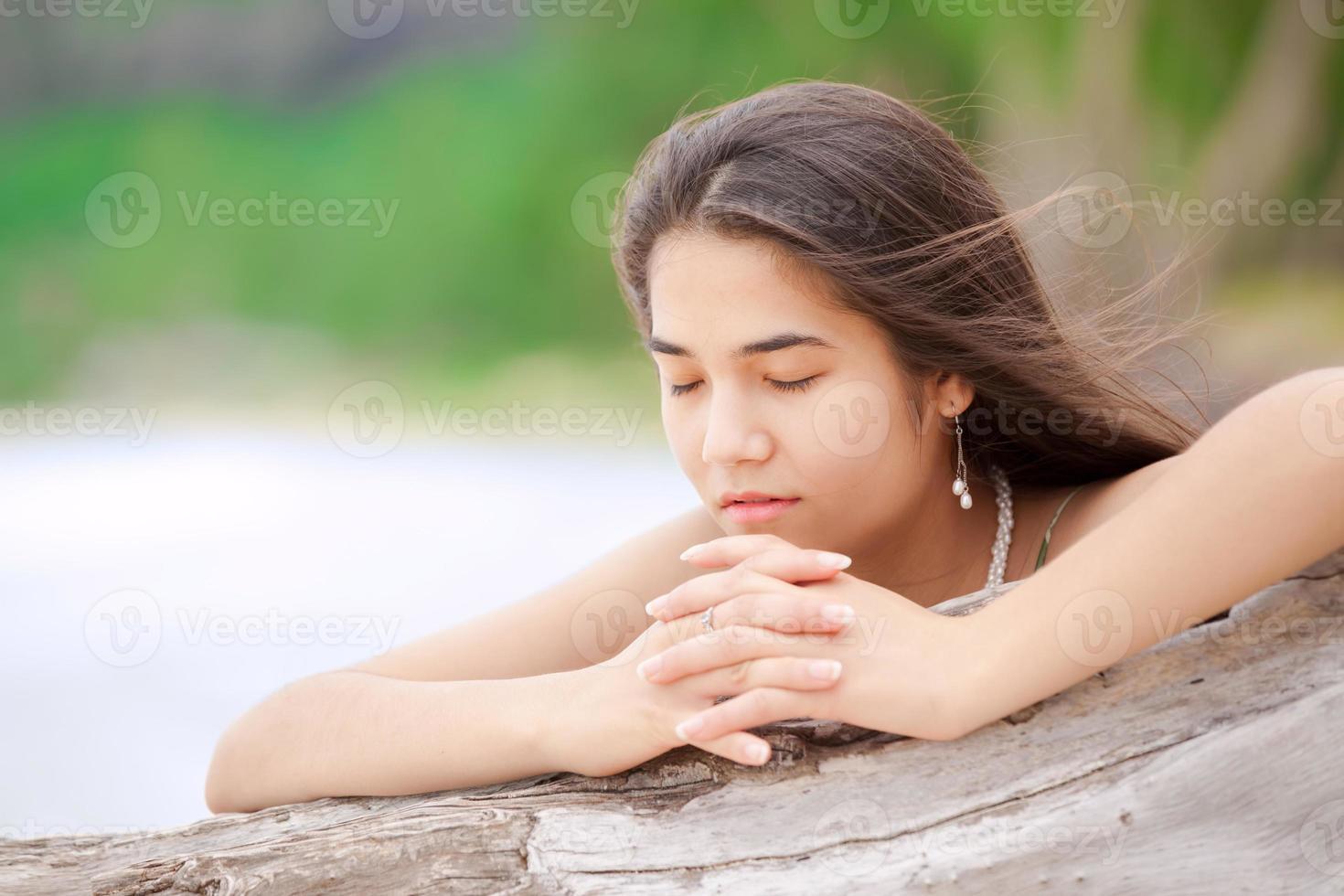 Hermosa jovencita en la playa rezando por el registro de madera flotante foto